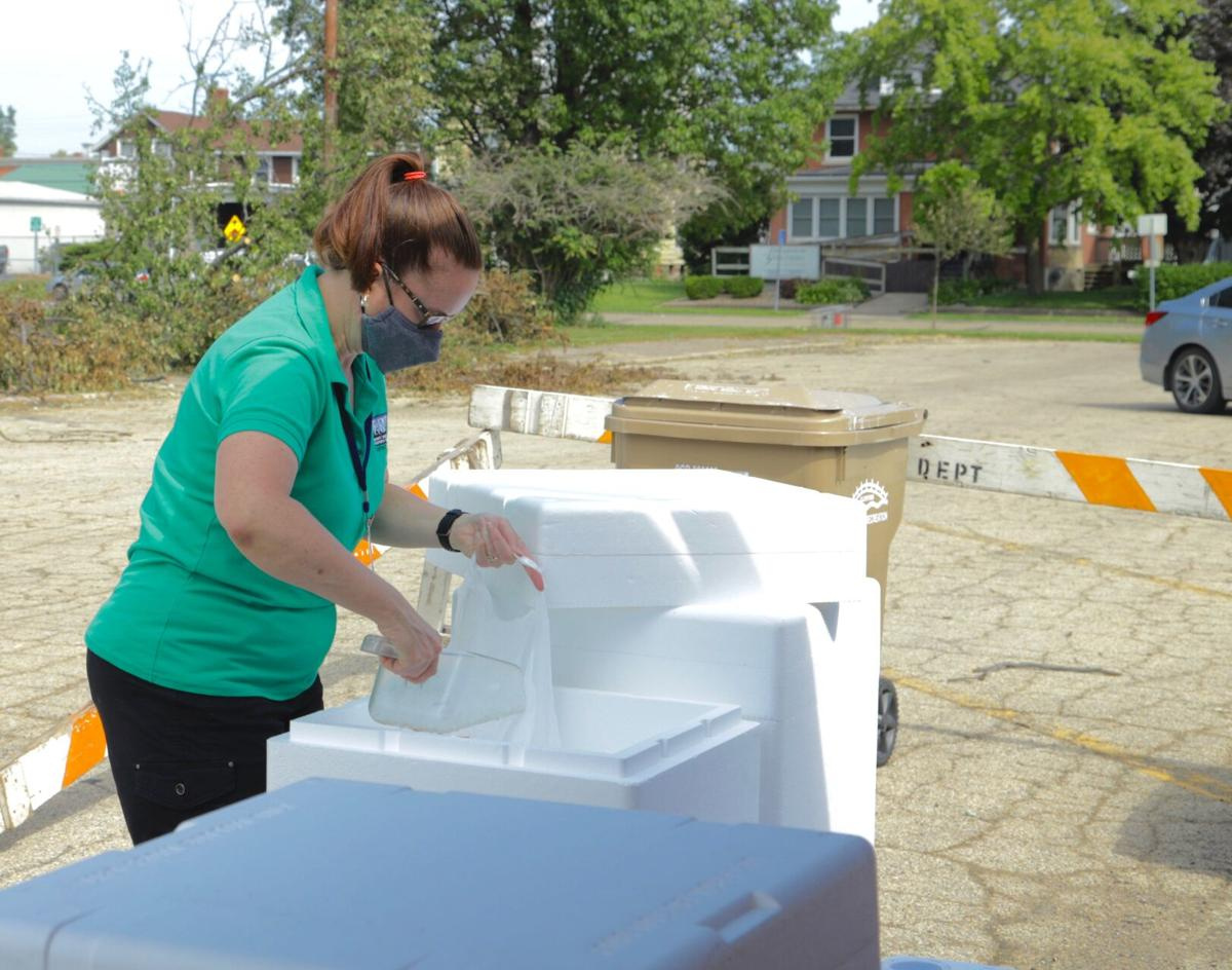 Tanya Van Lancker fills a bag with ice at the mobile resource center thursday