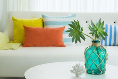 Modern design of living room with yellow,blue and orange pillow on sofa. Modern coastal home interior.