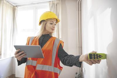 Female Surveyor With Digital Tablet Measuring Room With Laser Measure