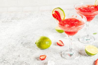 Cold strawberry margarita cocktail with ice, lime and fresh berries in margarita glass, light grey background copy space