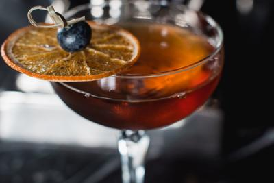 The Boulevardier Cocktail with orange chips on top. On a bar desk