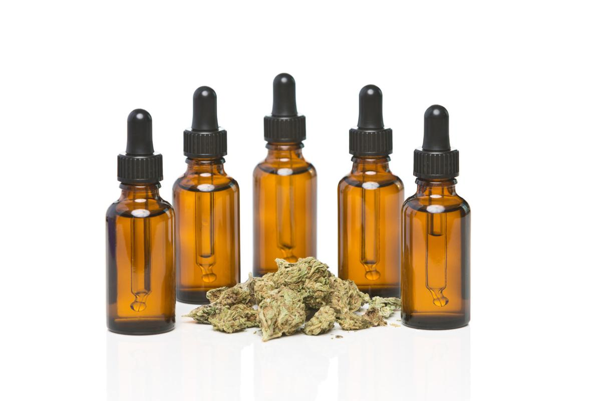 Five dropper bottles surrounding a pile of cannabis