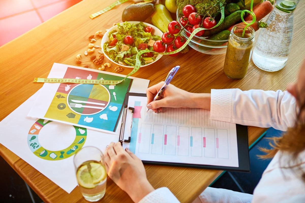 Woman dietitian in medical uniform with tape measure working on a diet plan sitting with different healthy food ingredients in the green office on background. Weight loss and right nutrition concept