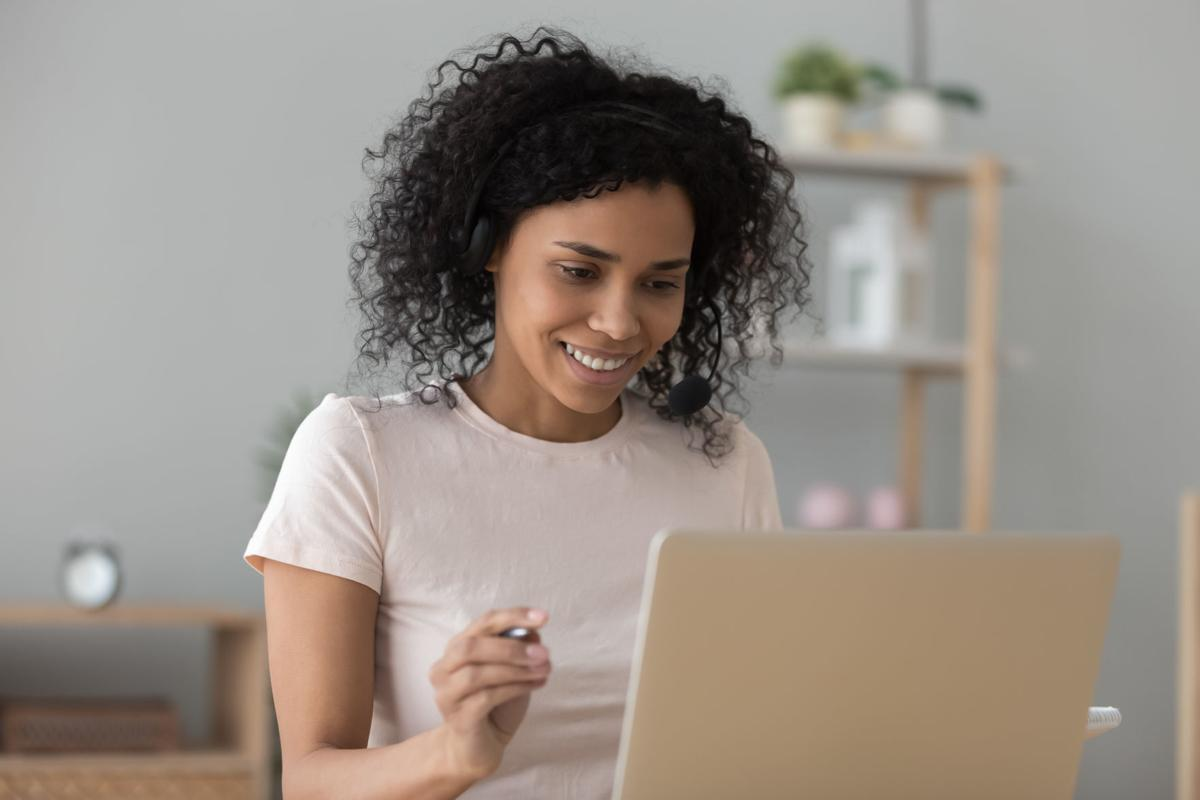 African woman looking at pc screen do task learning online
