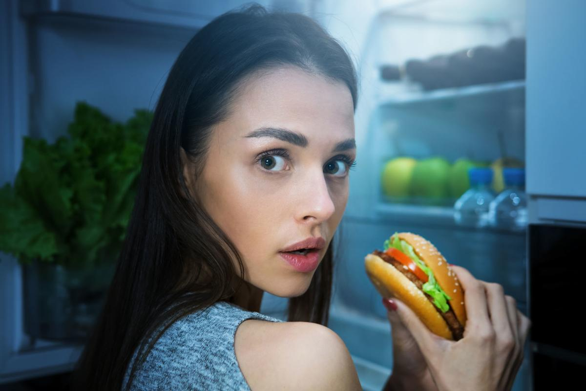 Hungry woman eating burger at night near fridge
