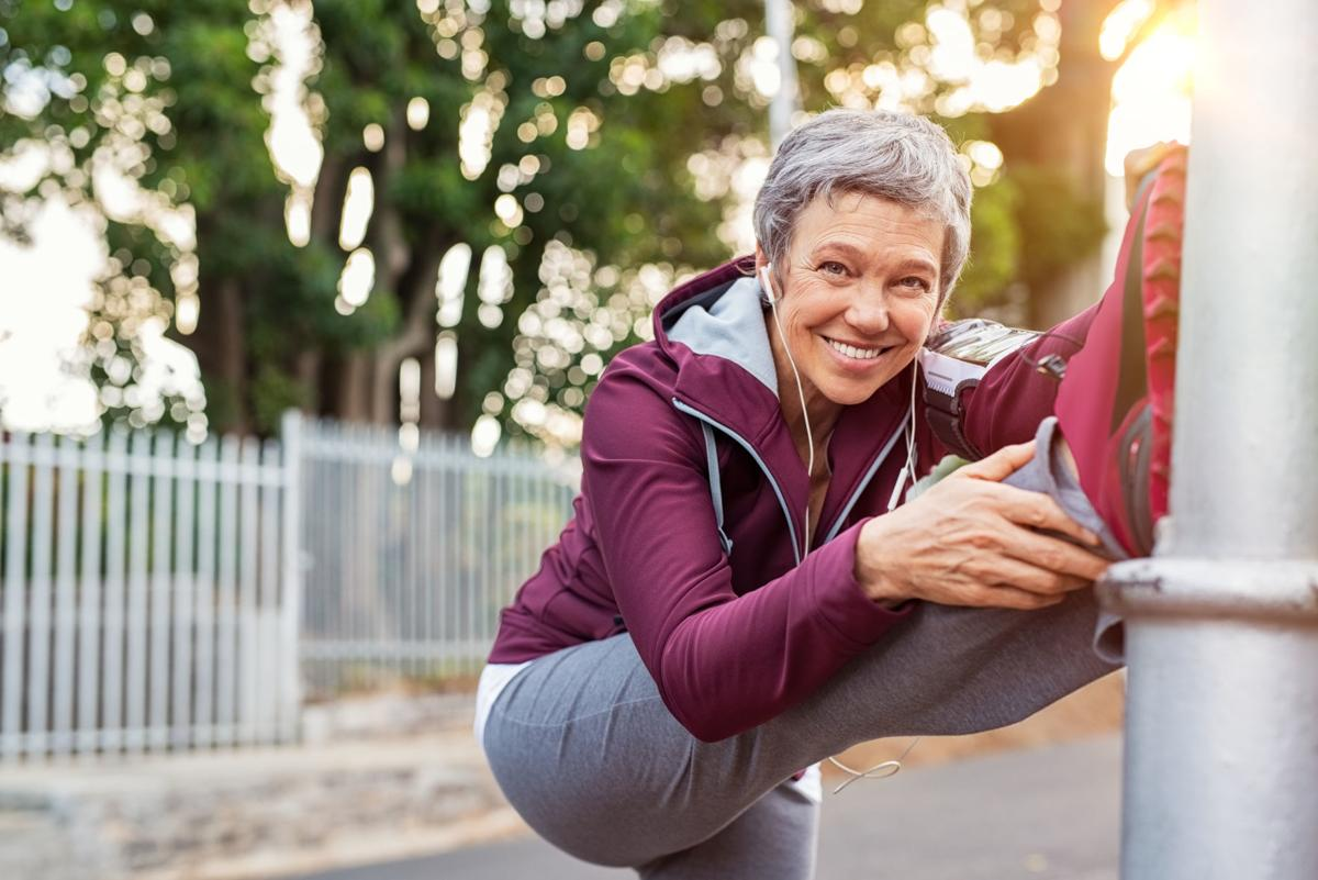 Mature woman warming up before jogging