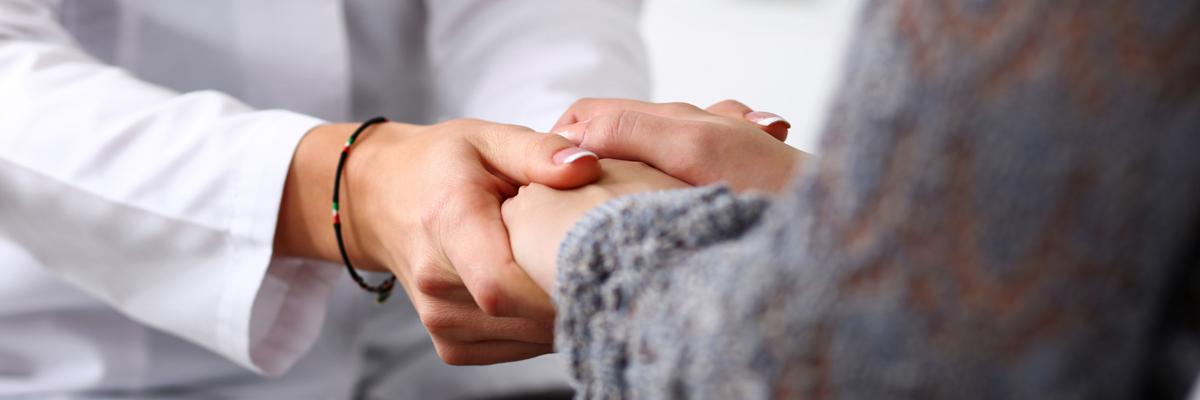 Friendly female doctor hold patient hand in office during reception