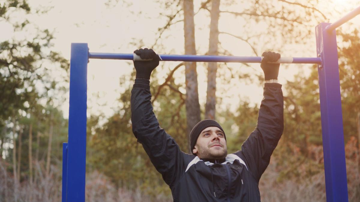 Young athletic man doing pull-up exercise in winter park outdoors