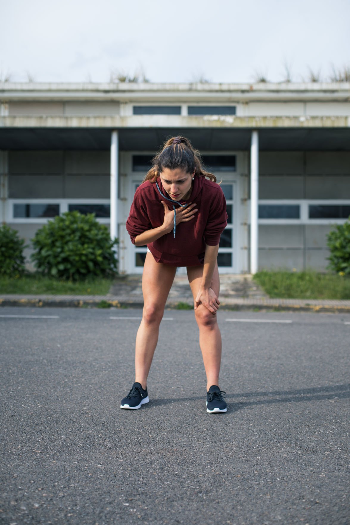 Female athlete suffering asthma attack during running training