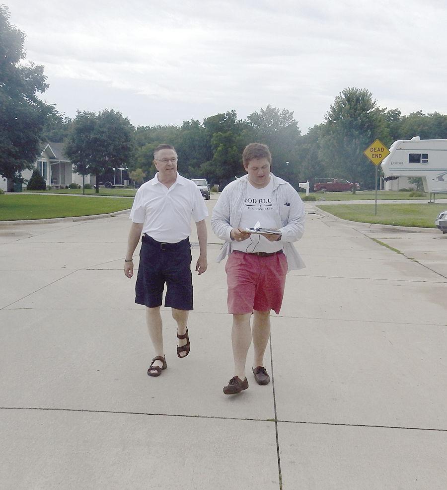 Congressman Rod Blum and Blum for Congress volunteer Brandon Borkey (right) travel door to door in Northeast Independence Tuesday afternoon asking for voter support.