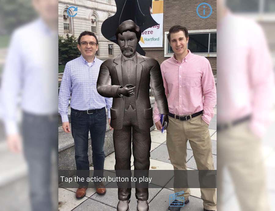 David Oyanadel (left) and Benjamin Williams appear to stand next to a digital statue of Mark Twain. The illusion is created on smartphones and tablets through the Hey Hartford app developed by Williams' and Oyanadel's company ARsome Technology.