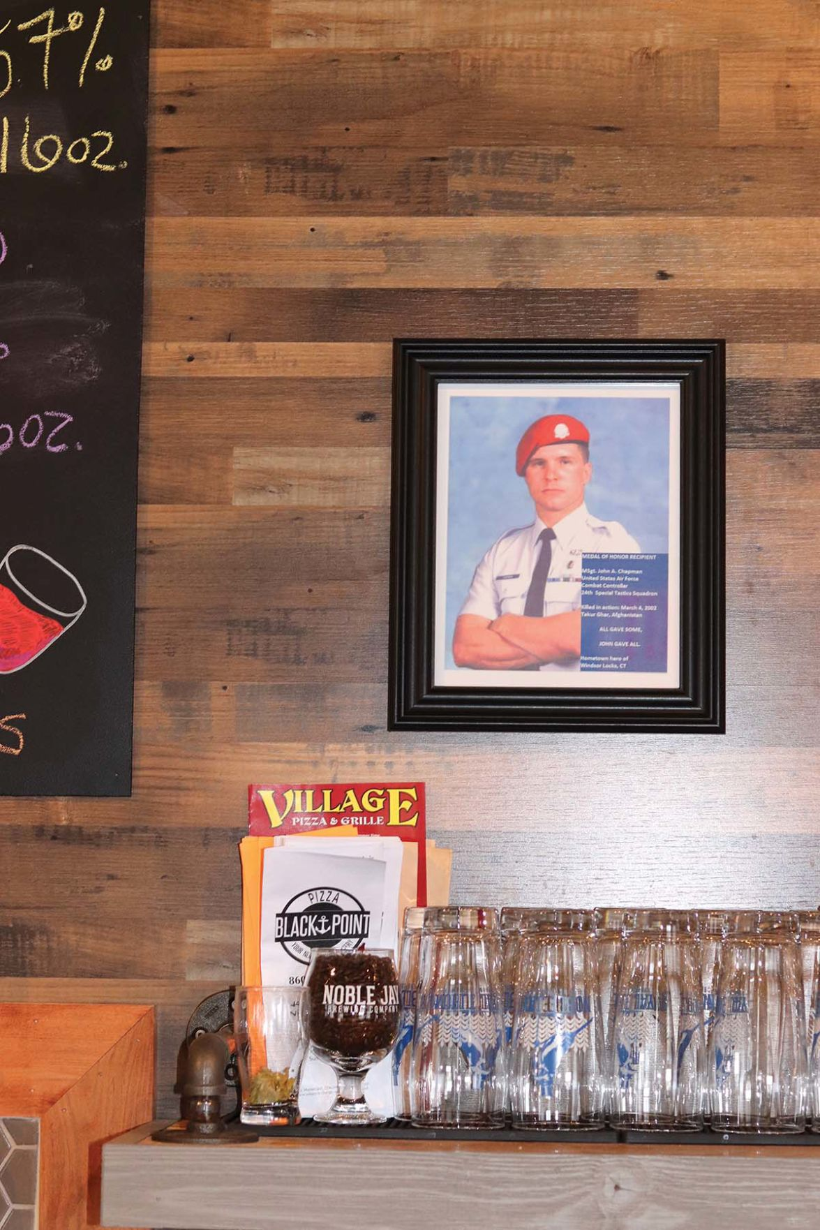 A photo of John Chapman hangs behind the bar at Noble Jay Brewing Co. in Niantic.