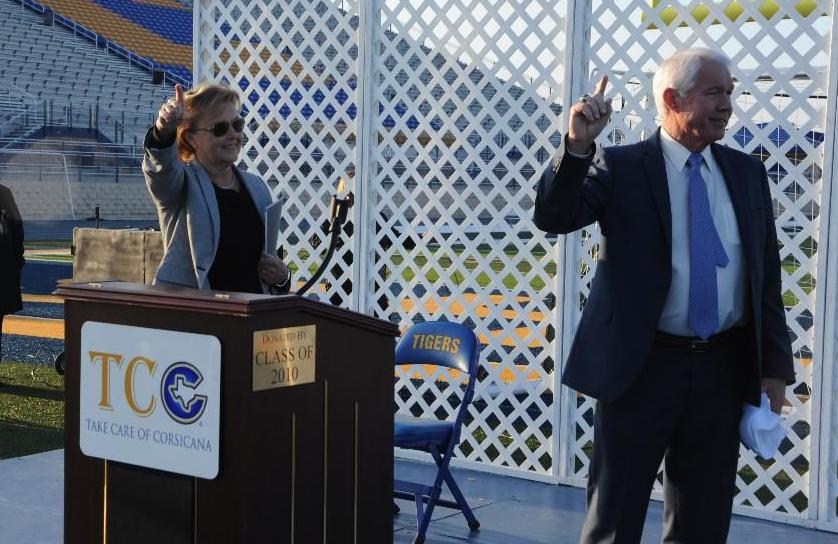 Hal Wasson (right) and Superintendent Diane Frost stand as the band plays the school song