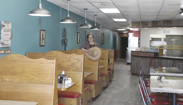 Sharon Anderson sits inside newly remodeled Outlaw Pizza on Corydon square
