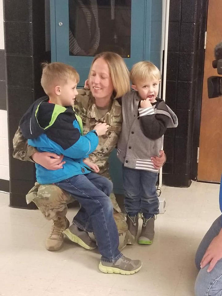 Amy Carpenter hugs her two boys Dane and Knox after surprising them at school following her return home