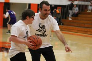 """<p>The WCHS Panthers and Canton Little Giants partnered together to hold the """"Unified Game"""" this past Friday, January 18. The game was a joint effort between the teams to feature players with and without special needs playing alongside each other in a game focusing on the spirit of inclusion and unity. (Above) Zach Davis, a coach for the Unified team, helps Trevor Kalke shoot a basket while warming up before the game.</p>"""