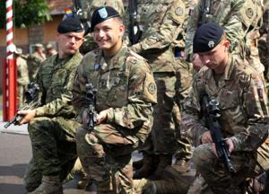 <p>Spc. Timothy Smith [center], a cavalry scout with Quickstrike Troop, 1st Squadron, 2nd Cavalry Regiment takes a knee with a Croatian and a U.K. soldier for a group photo after achieving top graduate during a Potential Noncommissioned Officer Cadre Course ceremony August 3, 2018 at Bemowo Piskie Training Area, Poland. Smith achieved top graduate and became the first U.S. soldier to achieve it. The two-week long course focused on command principles and was comprised of the practical application of these principles during a mixture of classroom instruction and infantry field exercises designed to develop leadership qualities of soldiers.The 2nd Cav. Regt. is on a six-month rotational assignment in support of the multinational battle group which is comprised of U.S., U.K., Croatian and Romanian soldiers who serve with the Polish 15th Mechanized Brigade as a defense and deterrence force in northeast Poland in support of NATO's Enhanced Forward Presence at BPTA.</p>