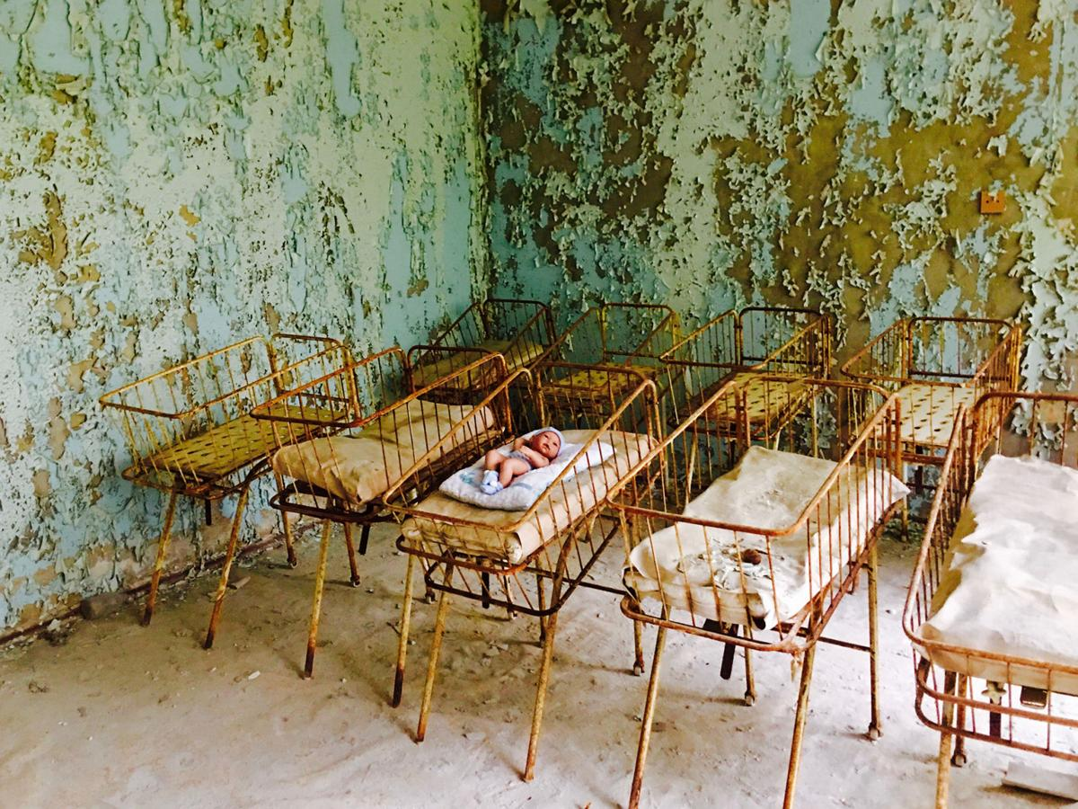 A rusting crib containing a baby doll and blanket sits in the Pripyat hospital maternity ward.