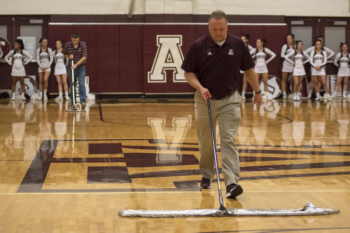 Ashland officials try to remove moisture from the gym floor surface.JPG