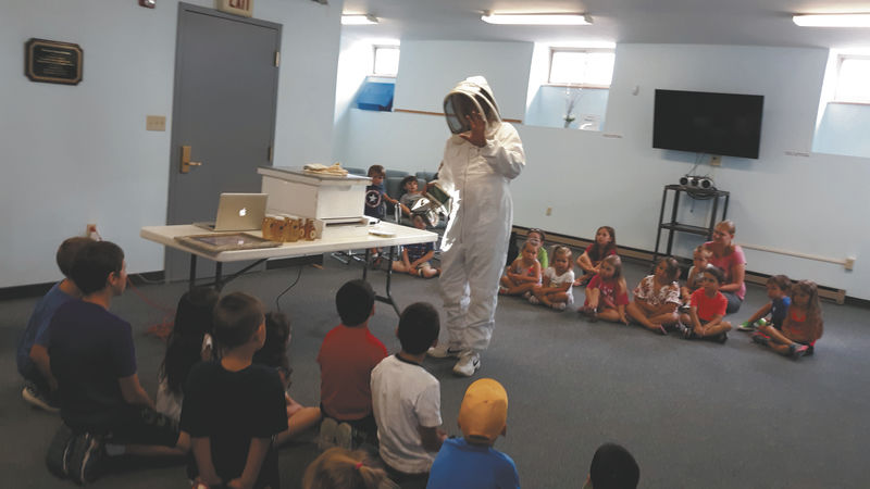 Beekeeper teaches kids about pollination, honey