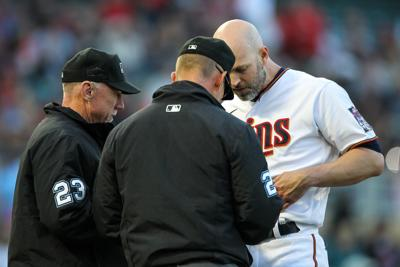 Umpires Lance Barksdale, left, and Jim Wolf search Minnesota Twins pitcher J.A. Happ for foreign substances in the third inning against the Cincinnati Reds at Target Field on June 21, 2021 in Minneapolis.