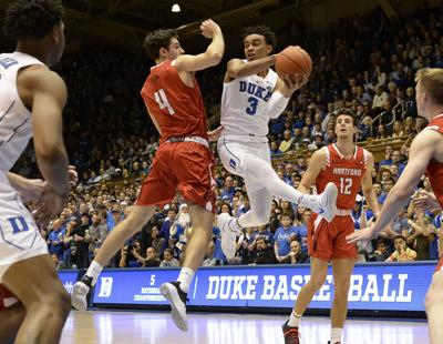 Duke guard Tre Jones (3) looks for help as Hartford forward George Blagojevic (4) defends in the first half at Cameron Indoor Stadium in Durham, N.C., on December 5, 2018.