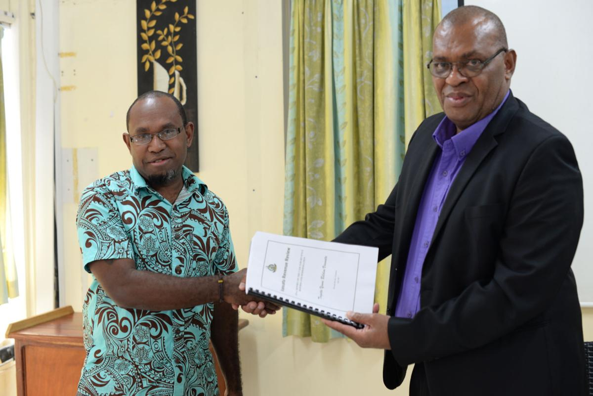 Chairman of the RRC Tony Sewen (l) presenting copy of the Report to Finance Minister Gaiton Pikioune (r)