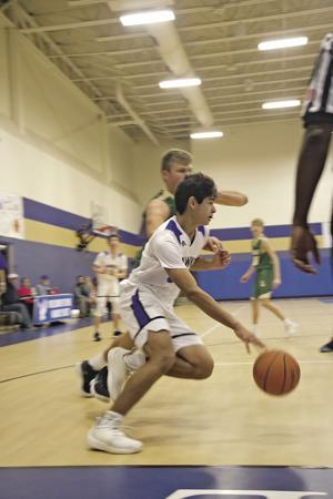 <p>OLH's James Ibarra drives for the basket along the base line.</p>