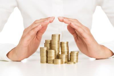 Savings protection, close up of female hands covering stack of golden coins