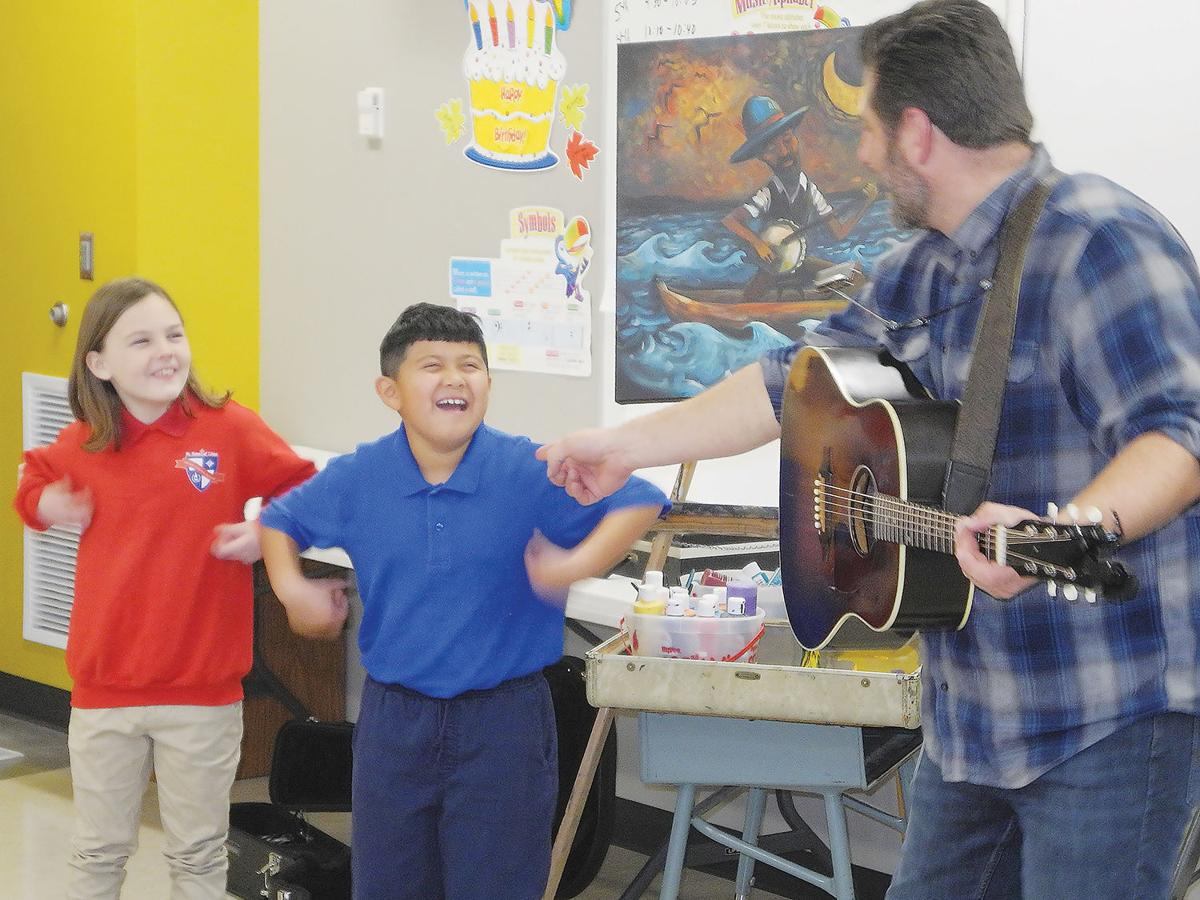 Chad Elliot with St. Rose students Tricia Collins and D'Angelo Mex