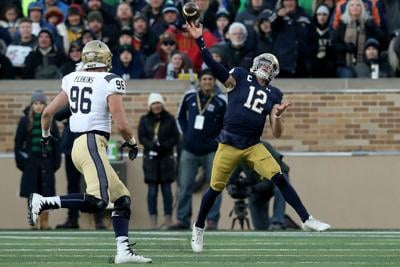Ian Book (12) of the Notre Dame Fighting Irish throws a pass while being chased by Jackson Perkins (96) of the Navy Midshipmen in the third quarter at Notre Dame Stadium on November 16, 2019 in South Bend, Indiana.