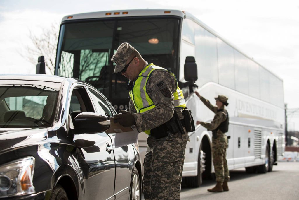 U.S. Army Reserve military police Soldier checks a driver's paperwork at one of the access control points