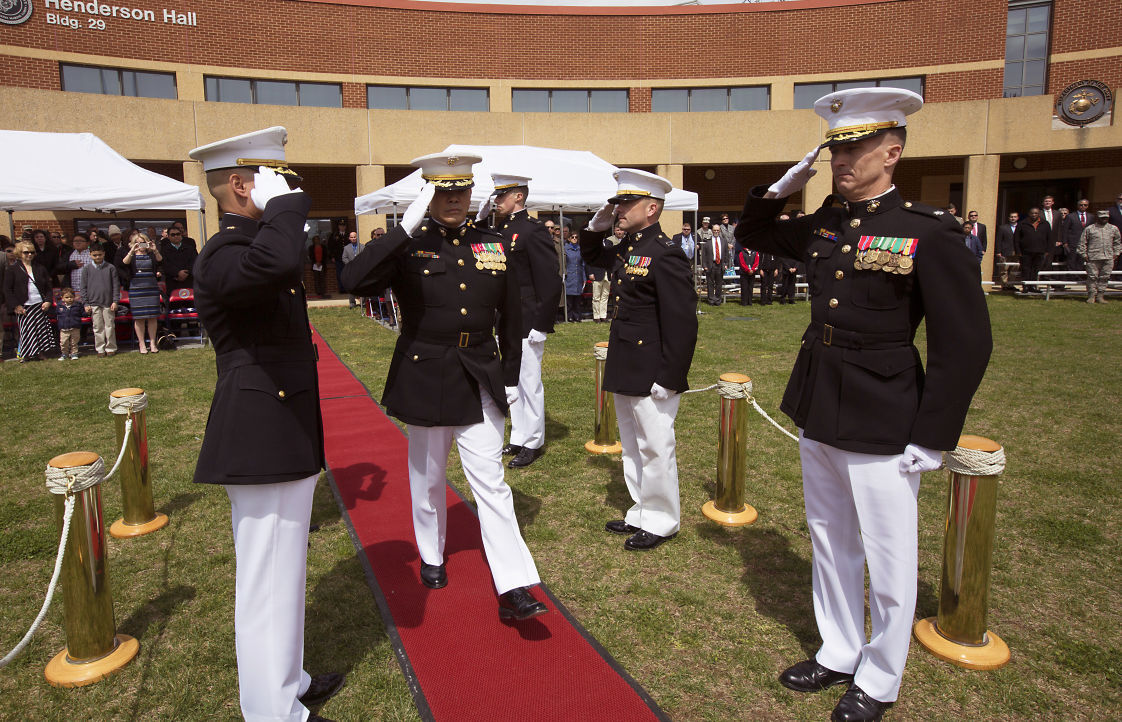 A cadre of his fellow Marine officers serving as side boys render salute
