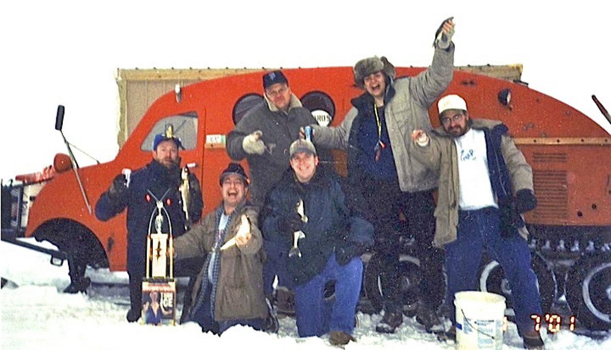 The Ice Fish gang poses with the coveted Fish Trophy for its annual group photo, probably in 2001, on Lake of the Woods. This year marked the 27th  consecutive year the group has gathered together.