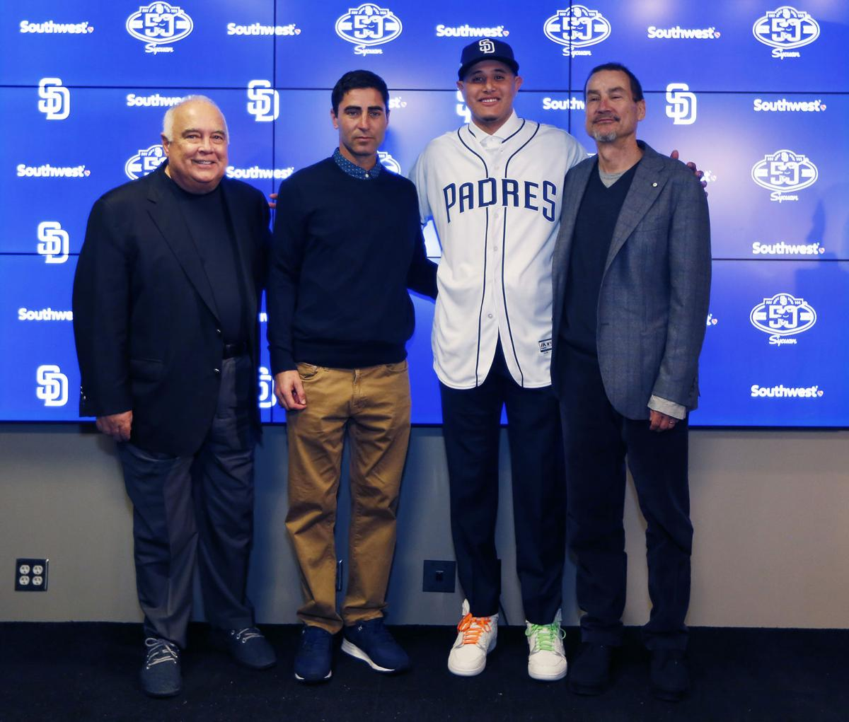 From left, San Diego Padres executive chairman Ron Fowler, general manager A.J. Preller, infielder Manny Machado and general partner Peter Seidler take a photo after a news conference on Friday, Feb. 22, 2019, in Peoria, Ariz. Machado agreed to a 10-year, $300 million contract with the Padres.
