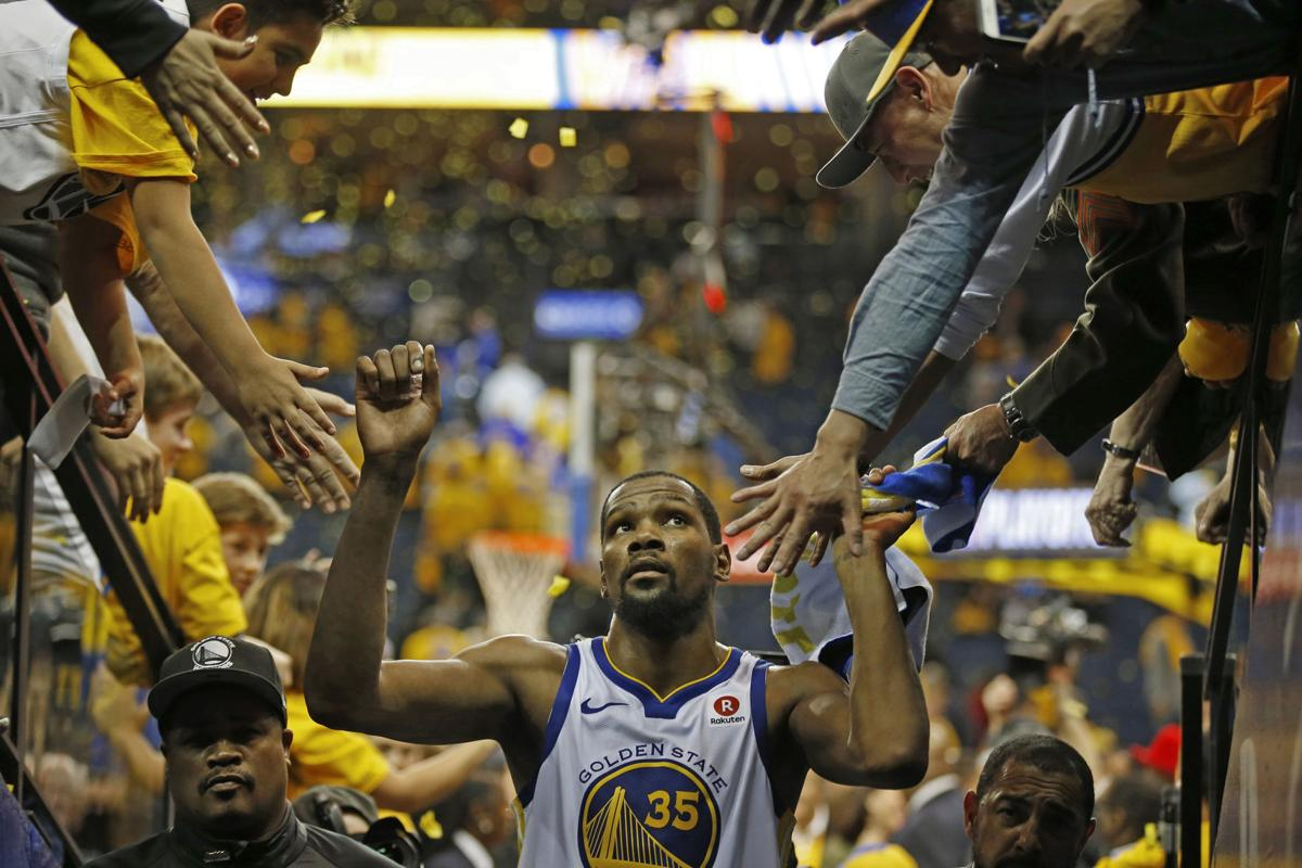 Golden State Warriors' Kevin Durant (35) is congratulated by fans as he exits the court after defeating the San Antonio Spurs during Game 5 of their NBA first round playoff series on Tuesday, April 24, 2018 at Oracle Arena in Oakland, Calif.