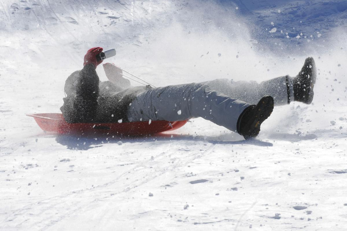Brendan Parisr, 20, of Derry tries to shoot video while he comes down the sledding hill during the 17th annual Frost Festival activities at Alexander Carr Park.