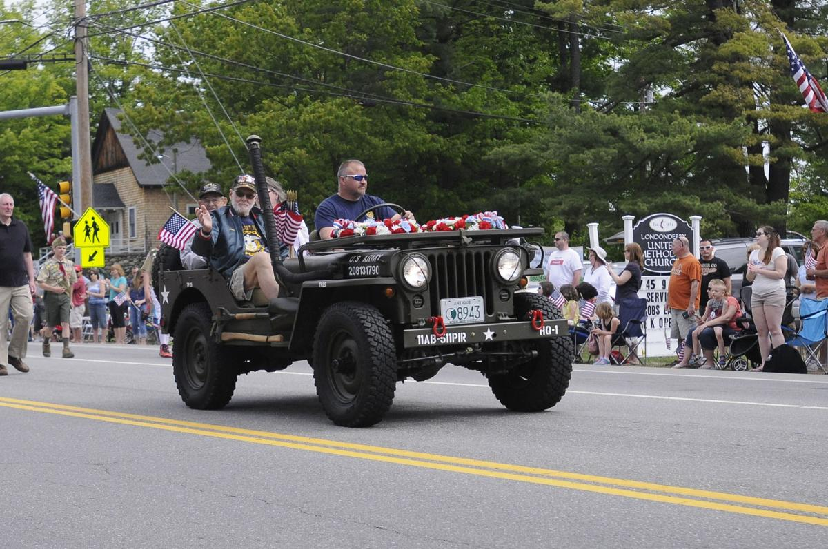 Veterans wave to the crowd from a military style Jeep as it drives along Mammoth Road during the Memorial Day Parade in Londonderry.