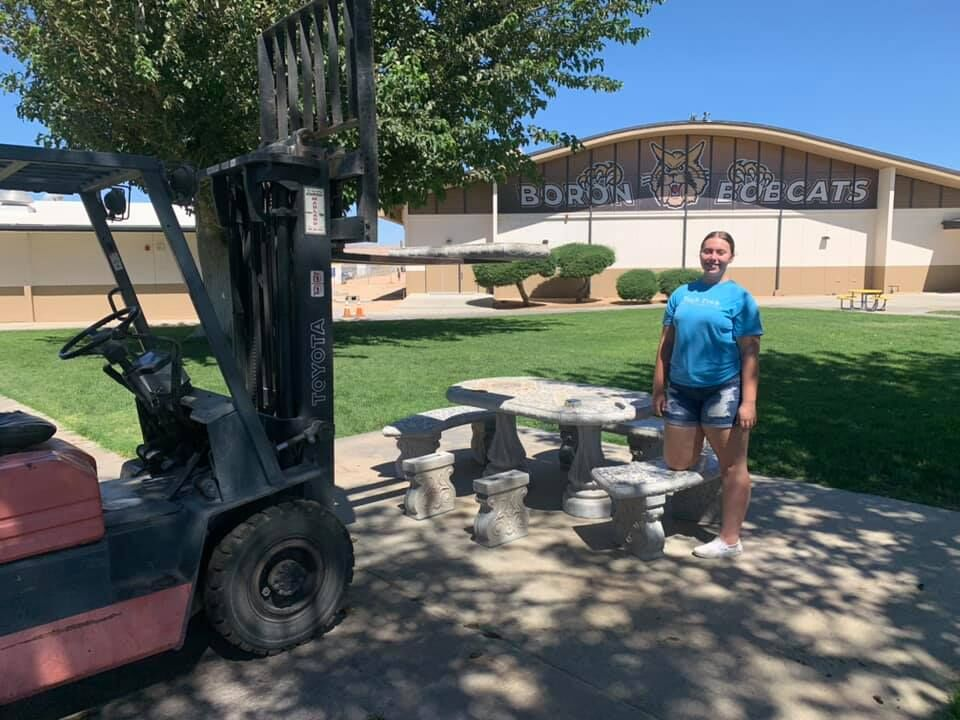 BHS senior Tatum Wiggs stands beside one of the completed tables at Boron Jr. Sr. High School
