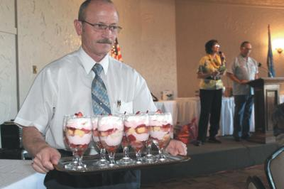 Duncan Chamber of Commerce President Chris Deal delivers a tray of desserts made by Dina Atnip, which were auctioned in the annual Bid Bash, held June 15. The event is a fundraiser for Food 4 Kids.