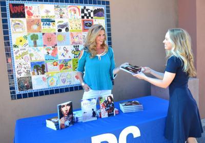 Chandler author Kate Mathias shows her latest book to Karli Regan.