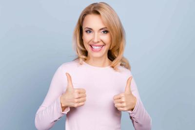 Portrait of pretty, charming, glad, nice woman with beaming smile showing two thumbs up sign with hands, isolated on grey background