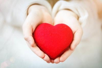 Red heart in hands of the little girl. Symbol of love and family.Valentines day card. Mother's day. Backgrounds for social posters. Selective focus.