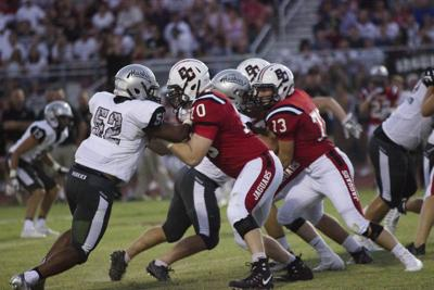 Hamilton's Derrick Porter attempts to put a move on Boulder Creek offensive lineman Preston Shepherd. Nationally, participation in high school football has dropped 15 percent.