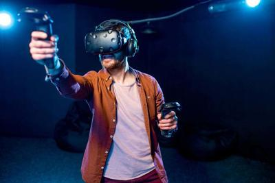Man playing game with virtual reality headset in the club