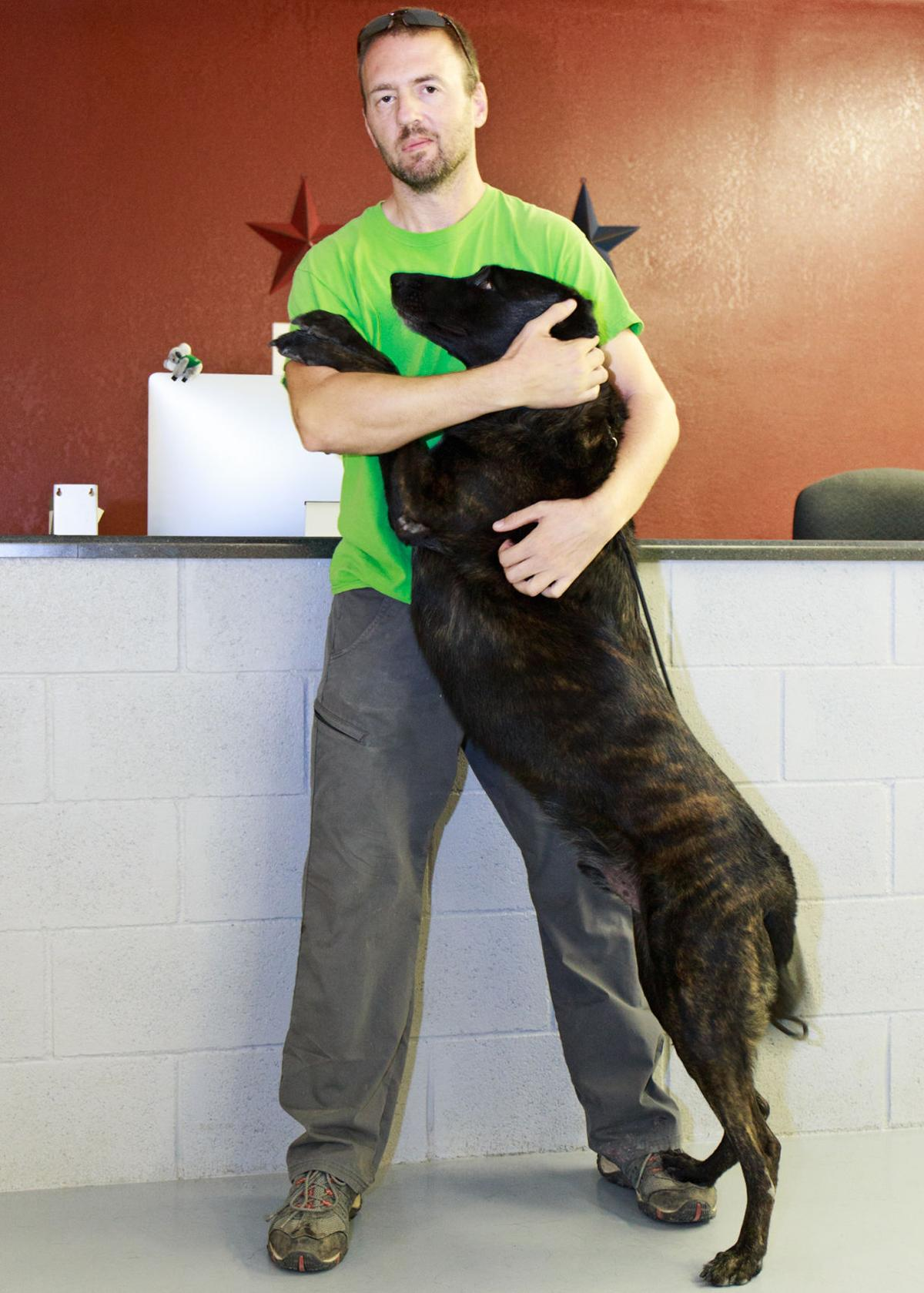 Nathan Braaten get a hug from Czar, a retired police dog