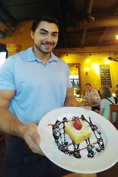 Caffe Boa server Marcelino Martinez displays one of the restaurant's classy desserts.