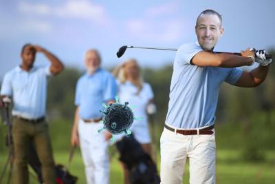 Male golfer following shot