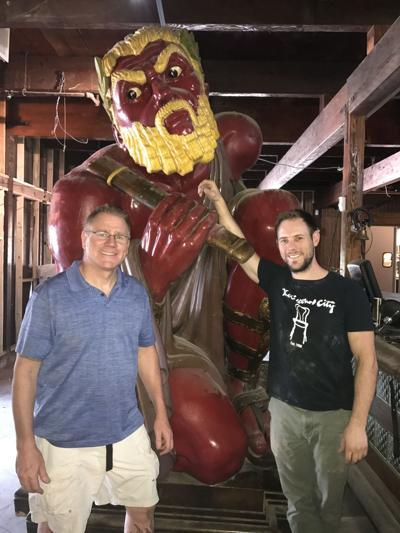 Erik Hoyer (left) and Mike Kenney show off a movie prop that hung from the rafters at Minder Binder. This Roman gladiator came from an MGM auction back in the 1970s.