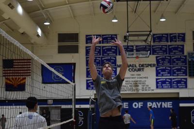 Senior Jonny Bowles sets a ball at Chandler High School volleyball practice.